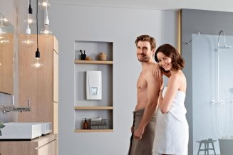 Ein Pärchen in einem modernem Bad schaut lächelnd in die Kamera, während der Durchlauferhitzer Clage DSX Touch im Hintergrund an der Wand montiert ist.