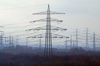 Strommasten in der Abenddämmerung umgeben von Nebel