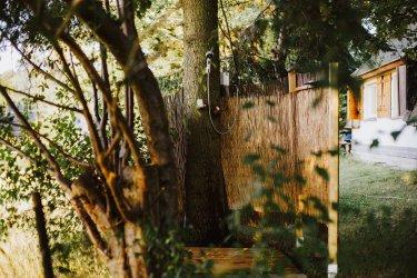 Tragbare Dusche mit Cointra Durchlauferhitzer in einem Garten an einen Baum montiert