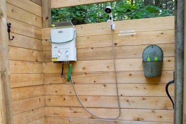 Außendusche mit Eccotemp Durchlauferhitzer in einem Holzverschlag in der Natur
