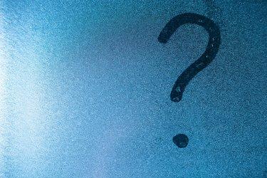 Ein mit dem Finger auf eine beschlagene Glasscheibe geschriebenes Fragezeichen.