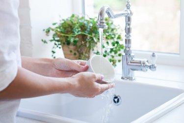 Frau beim Spülen einer Tasse