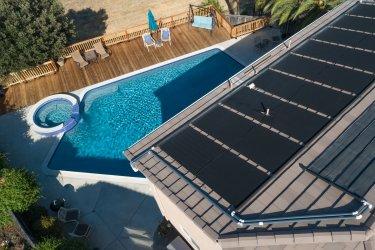 Ein Garten mit Pool und Solarpanelen auf einem Dach