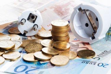Stromkabel auf Geldscheinen und Euromünzen liegend