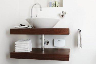 Kleindurchlauferhitzer Vaillant miniVED unter einem modernem Waschbecken zwischen zwei Regalbrettern hängend