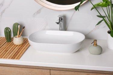 Ein modernes Waschbecken auf einem Waschtisch umgeben von Deko in Braun- und Grüntönen.
